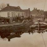 Laden van een schip met aardappelen aan de thans Kerkstraat te Haulerwijk. De molen op de achtergrond draaide met twee wieken.